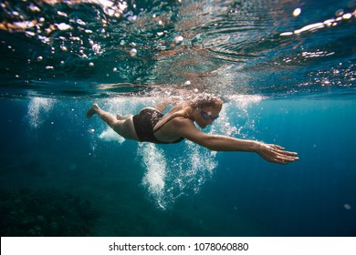 Professional female swimmer swim in the ocean on the sunrise, underwater picture