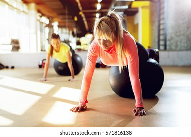 Professional female trainer at gym working push ups with pilates ball.
