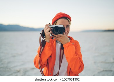 Professional female traveler focusing lenstaking picture of wild environment in national park during journey expedition,woman blogger using modern digital camera for making photos of scenery landscape