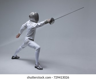 Professional fencer in fencing mask attacking on grey background