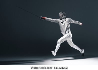 Professional fencer in fencing mask with rapier jumping on grey