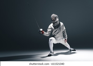 Professional fencer in fencing mask with rapier standing in position on grey