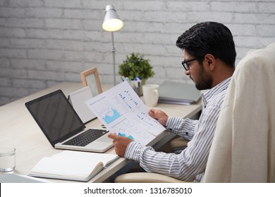 Professional financial analyst sitting at tablet in his office and checking statistics in documents