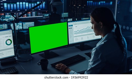 Professional Financial Data Analysts Working on a Computer with Green Screen in Modern Monitoring Office with Live Analytics Feed on a Big Digital Screen. Monitoring Room with Finance Specialists.