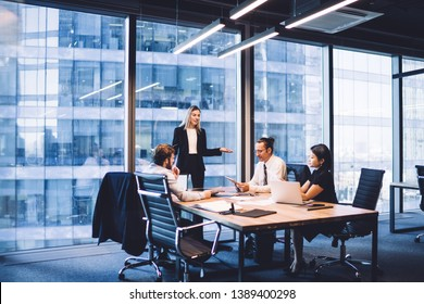 Professional financial experts collaborating during brainstorming meeting listening information from clever female director, businesswoman providing information to corporate workers of company
