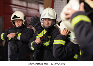 Professional firefighters wearing uniforms and putting on gloves and protective helmets. Getting ready for action. Firetruck in the background.