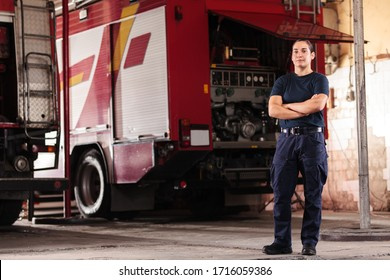 Professional fireman portrait. Female firefighter wearing uniform of shirt and trousers. Fire truck in the background.