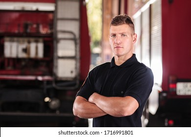 Professional fireman portrait. Firefighter wearing shirt uniform and fire truck in the background.