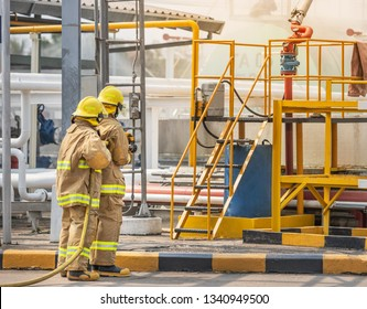 professional firemans brave buddy team assistance in yellow fire fighter uniform holding fire hose nozzle fighting with fire flame in the industrial factory