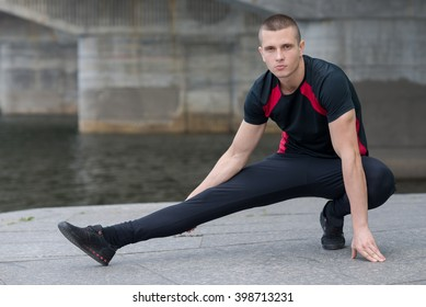 Professional fitness trainer. Male sportsman is training himself. Outdoors workout fitness concept.