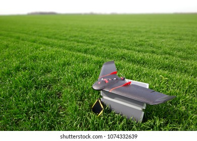 Professional fixed wings drone for agriculture, placed on its transport case in the wheat field, next to a tablet computer for remote control during flight