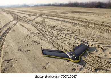 Professional fixed wings drone laying on its belly, after successful landing on a sand surface of a road construction site