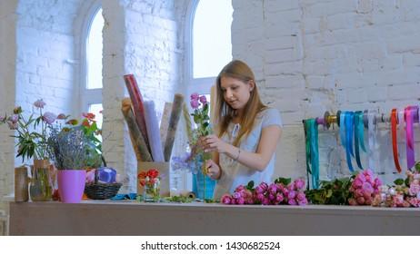 Professional floral artist, florist cutting flowers at flower shop, workshop. Floristry, handmade and artwork concept