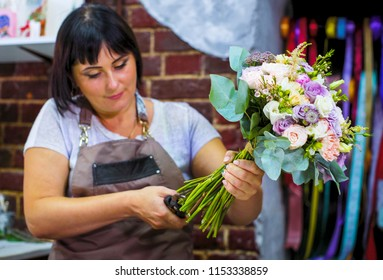 professional florist cutting flower stems with scissors in wedding bouquet in studio. Caucasian female master in apron creating floral composition. Floristry, handmade and small business concept