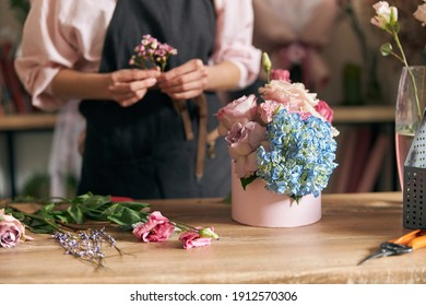 Professional florist young woman is doing bouquets at flower shop