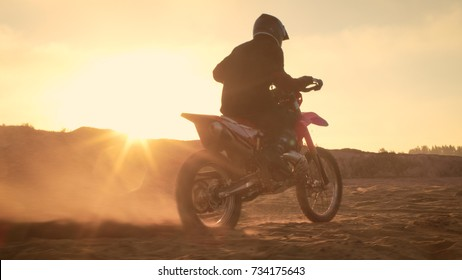 Professional FMX Motorcycle Rider Twists Full Throttle Handle and Starts Riding on the Sandy Off-Road Track. Scenic Sunset.