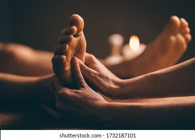 Professional foot massage close up. Authentic shot of luxury spa treatment. Charming light. Shallow depth of field. Stylized and colored.