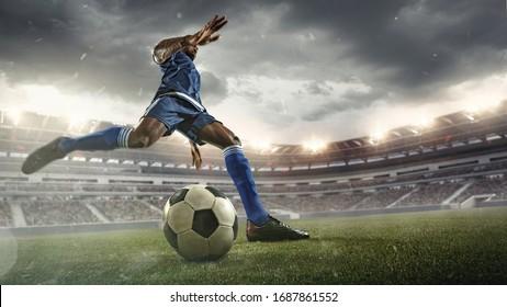 Professioneller Fußball- oder Fußball-Spieler in Aktion auf dem Stadion mit Taschenlampen, Kickball für das Siegerziel, Weitwinkel. Konzept des Sports, des Wettbewerbs, der Bewegung, der Überwindung. Feldpräsenz-Effekt.