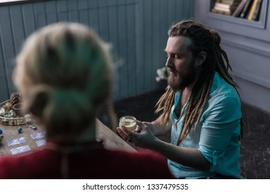 Professional fortuneteller. Nice bearded man focusing on his work while being a fortuneteller