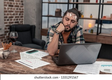 Professional freelancer. Pleasant thoughtful man looking at the laptop screen while focusing on his work