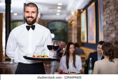 Professional friendly smiling pleasant waiter holding serving tray for restaurant guests