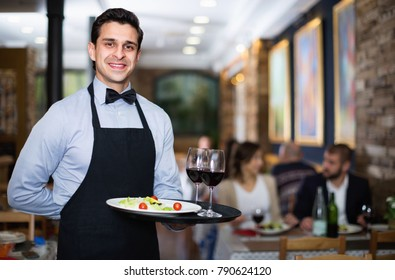 Professional friendly waiter holding serving tray for restaurant guests