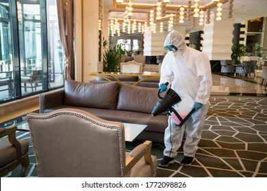 Professional fully armed disinfector against Covid-19 (coronavirüs, pandemic) using sprays to remove bacteria from the surface at the hotel. Man wearing a protective mask, gloves and suit.