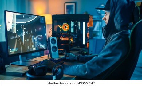 Professional Gamer and Streamer Playing First-Person Shooter Online Video Game on His Cool Personal Computer. Young Man is Wearing a Cap and Hood. Room and PC have Colorful Neon Led Lights.