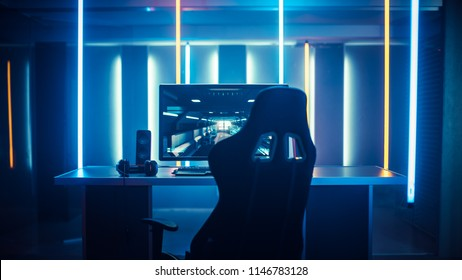 Professional Gamers Room With Ultra Powerful Personal Computer. Paused First-Person Shooter Game on Screen. Room Lit by Neon Lights in Retro Arcade Style. Cyber Sport Championship.