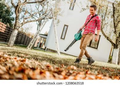 Professional gardener using leaf blower and working in garden