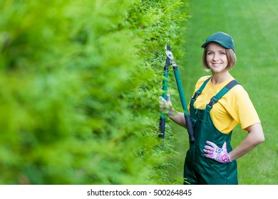 professional gardener at work. smiling young woman gardener working with lopping shear in the yard. garden worker trimming plants. topiary art. gardening service and business concept