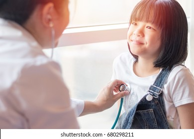 Professional general medical pediatrician doctor in white uniform gown listen lung and heart sound of Asia child patient with stethoscope: Physician check up Asian kid female after consult in hospital