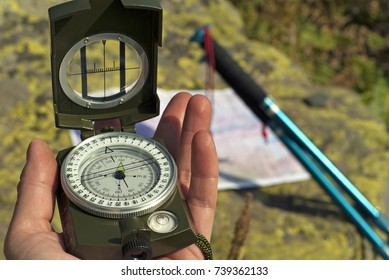 Professional geological compass in the man`s hand closeup. On a blurry background can distinguish a map spread out on a stone and leaning poles for a nordic walking.