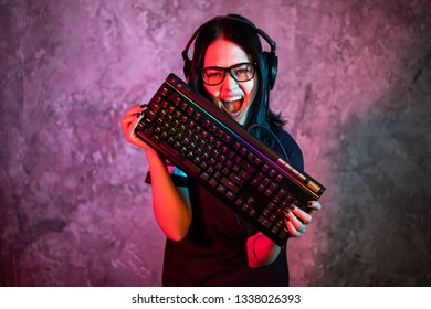 Professional Girl Gamer in MMORPG Strategy Video Game. She's She posing over colorful blue and pink background with a gaming keyboard. She Wears Gaming Headset.