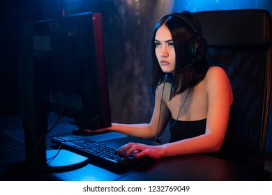 Professional Girl Gamer Plays in MMORPG or Strategy Video Game on Her Computer. She's Participating in Online Cyber Games Tournament, Plays at Home, or in Internet Cafe. She Wears Gaming Headset