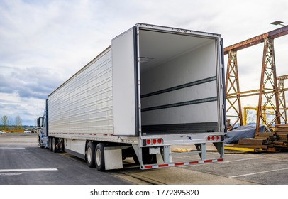 Professional grade Big rig blue semi truck with open door empty semi trailer standing at warehouse parking lot at industrial area waiting for the commercial load for the next delivery