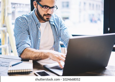 Professional graphic designer working on laptop computer creating project spending time in coworking office,skilled male it developer typing on netbook updating software doing remote job in cafe