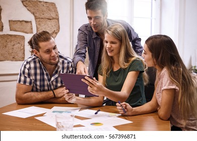 Professional group of millenials in a conference room looking and pointing excitedly at tablet pc that one of the ladies is holding up for all