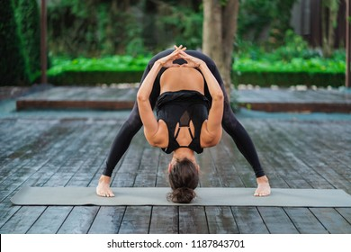 Professional gymnast fitness instructor doing Uttanasana standing barefoot on yoga mat. Flexible woman stretching forward, head inclination to legs. healthy lifestyle concept.