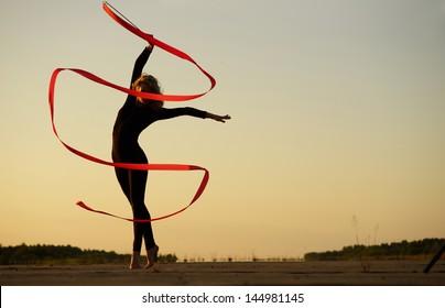 Professional gymnast woman dancer posing with ribbon