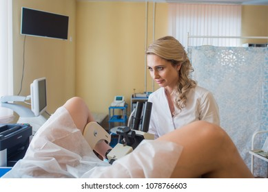 Professional gynecologist examining her female patient on a gynecological chair.