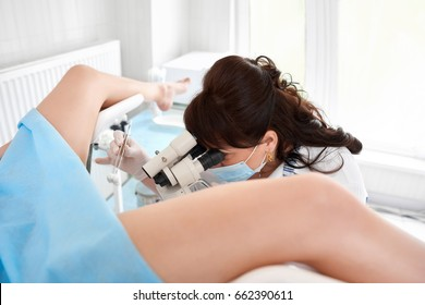 Professional gynecologist examining her female patient on a gynecological chair