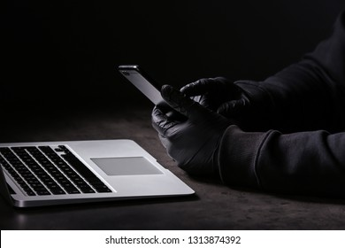 Professional hacker with laptop and mobile phone sitting at table on dark background