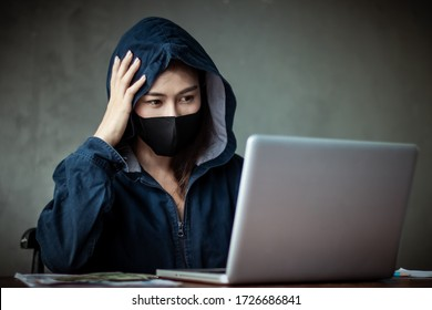 Professional hacker women Wearing a blue shirt with a hood Stealing data from online computer systems By releasing viruses into the system By using laptops and keyboards concept of malware and hacker