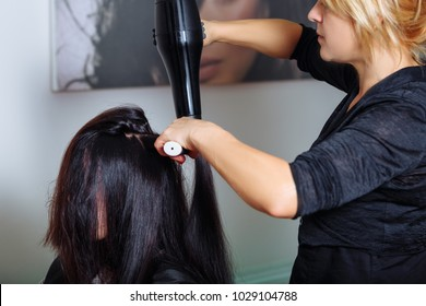 Professional hair stylist with hairdryer and comb working at customer's hair. Horizontally framed shot.