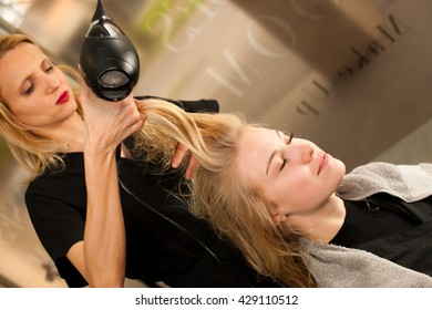 professional hair stylist at work - hairdresser  doing hairstyle to  beautiful young blonde customer in a professional studio