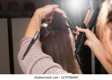 professional hairdresser clipping hair of a young model with a hairpin before making a corrugating coiffure in a beauty salon