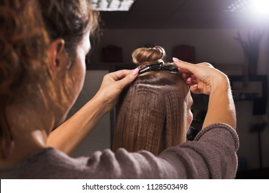 professional hairdresser clipping a hairdo with a topknot using a hairpin to a young woman in a beauty salon. concept of carefull hair treating