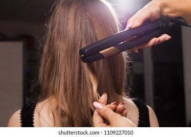 professional hairdresser curling a hair strand of a model with relaxed hair in a beauty salon. concept of stylist training