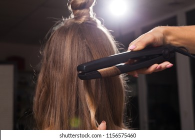 professional hairdresser curling a hair strand of a girl with a topknot in a beauty salon. concept of stylist training